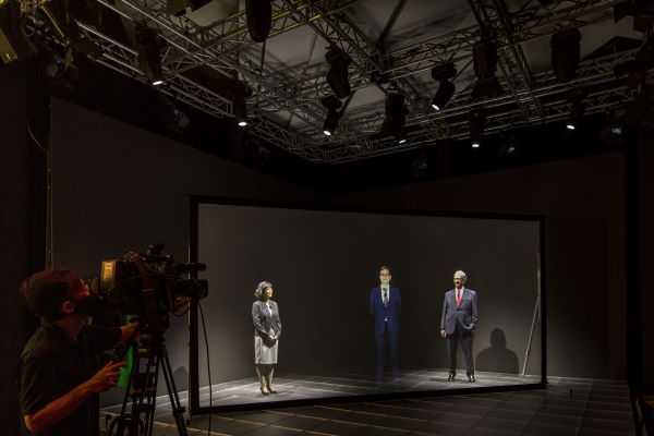 A woman and two men in a holographic studio